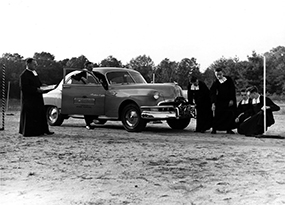 Six Christian Brothers investigate the distance of a Pontiac car from a pole