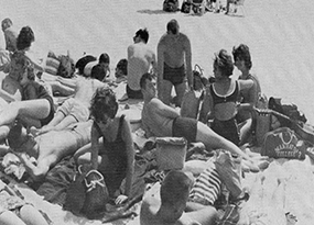 Manhattan College boys and girls lay out in the sun on a beach in 1962