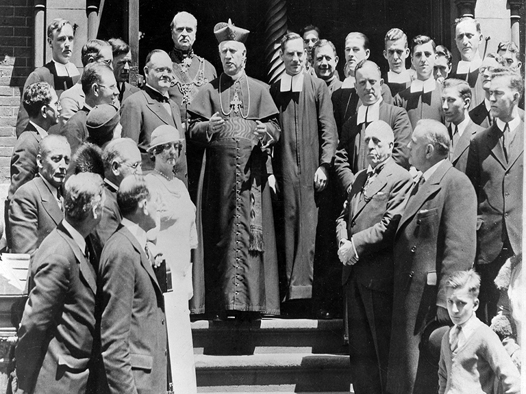 A man in religious clothing stands in steps speaking to other men