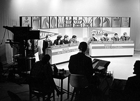 4 Manhattan College male students and 4 Citadel male students are seated at 2 tables in a television studio preparing to film the quiz show competition the College Bowl in March 1970.