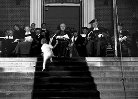 A toddler interrupts the Commencement ceremony by climbing up the chapel steps.