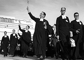 Six Christian Brothers dressed in their habits walk down an airplane runway surrounded by a crowd of people, carrying luggage bags and waving their hands and a flag.