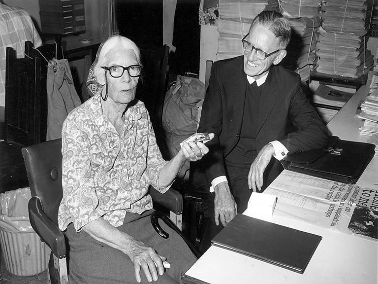 woman with white hair and glasses sitting with man with glasses