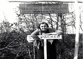 "A women leans on a sign that says ""Packer"" while standing under a sign that reads ""Morning Glory Trout and Game Preserve: Private""."