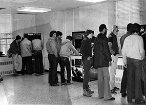 A handful of male students gather around three video game machines in Thomas Hall.