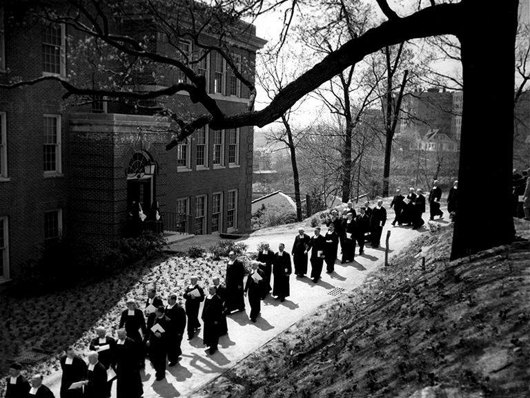 A procession of men walking outside on campus as part of Manhattan's centennial anniversary in 1953.