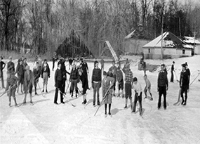 A bunch of young boys play ice hockey in the cold on a pond at St. Joseph's Normal Institute in Pocantico Hills, New York.