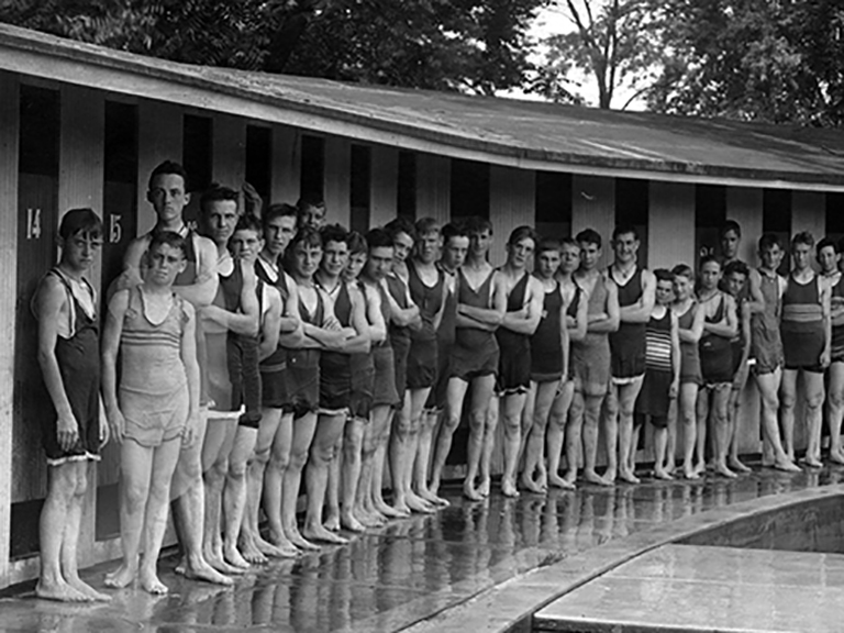 A group of young men standing next to a swimming pond.
