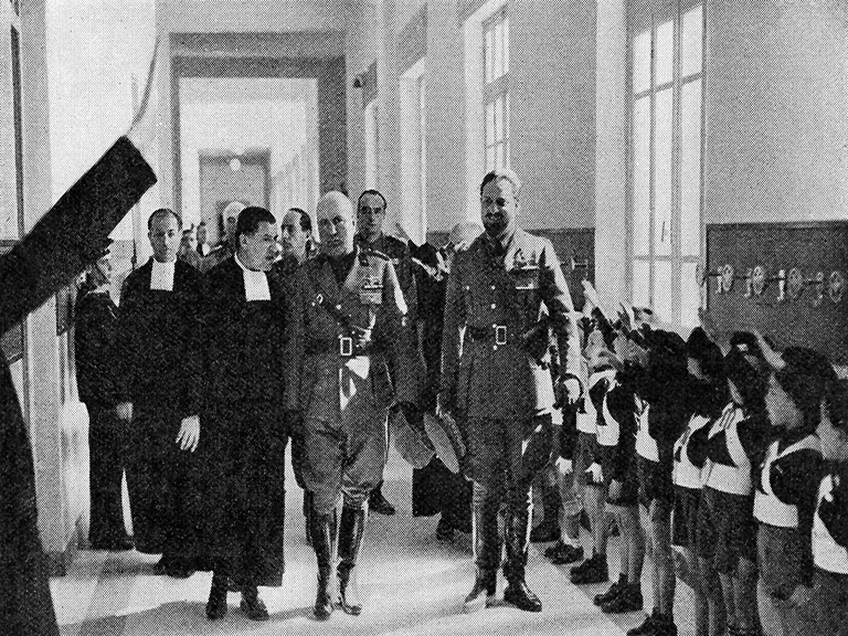 Benito Mussolini walks in a school with Christian Brothers