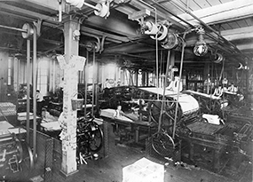 An industrial warehouse with large, rotary printing presses manned by young boys at the New York Catholic Protectory, circa 1900.