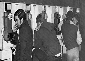 Three young men stand at a payphone bank and talk on the phone, with their backs to the camera.