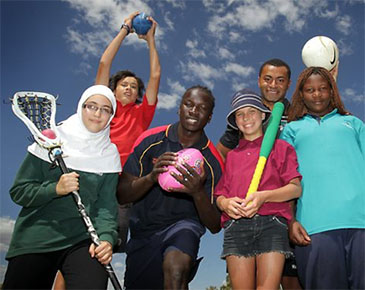 Group of children in uniforms with sports equipment