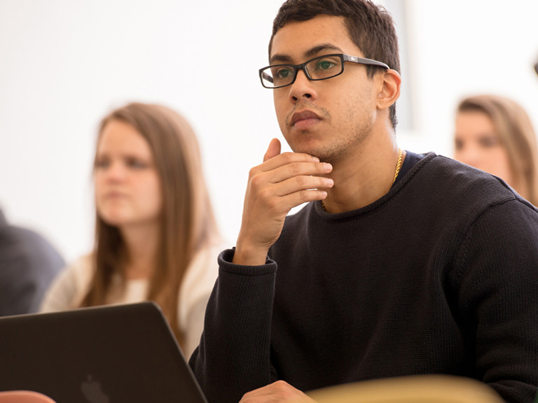 male student looking pensive while listening to lecture