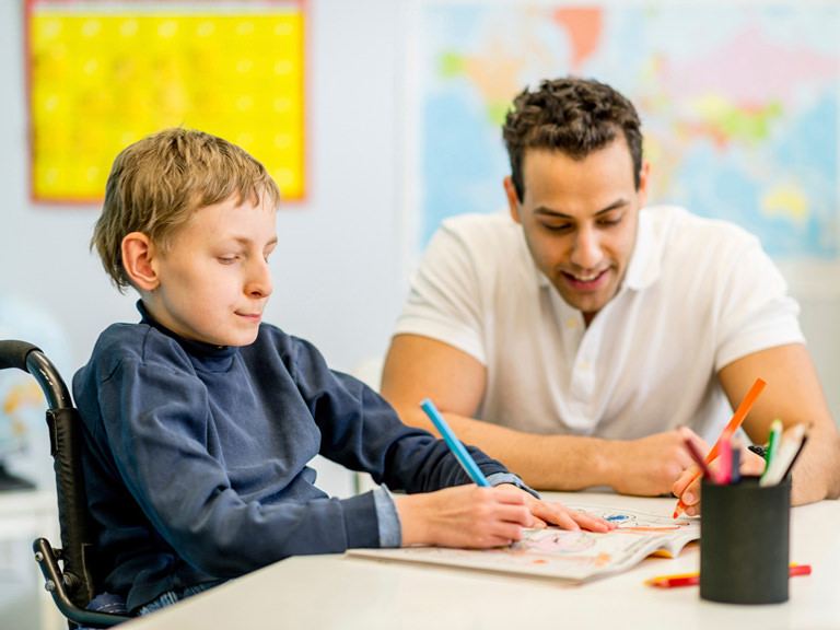 Teacher works with disabled student.