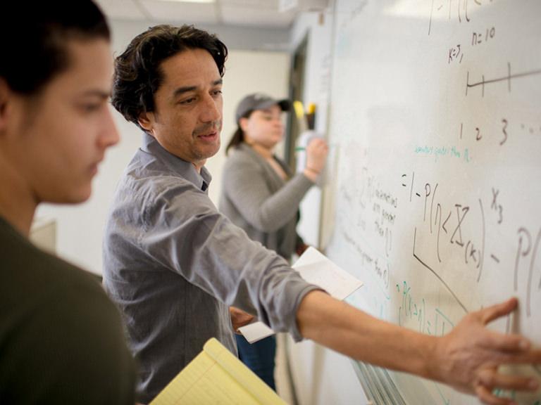 Teacher writes formulas on the board.