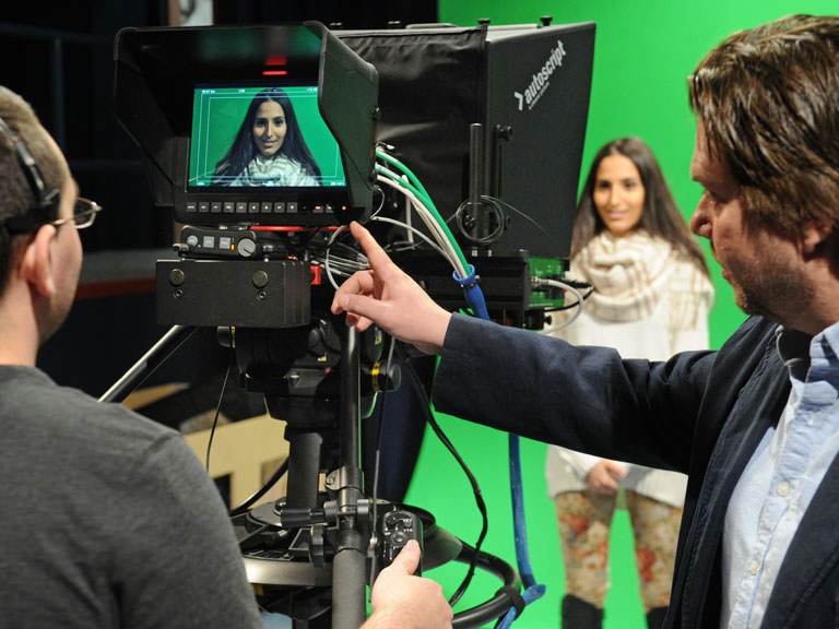 Students and professors collaborate in the broadcast studio.