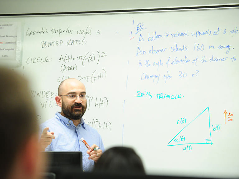 A professor gives mathematics lecture to a classroom full of students.