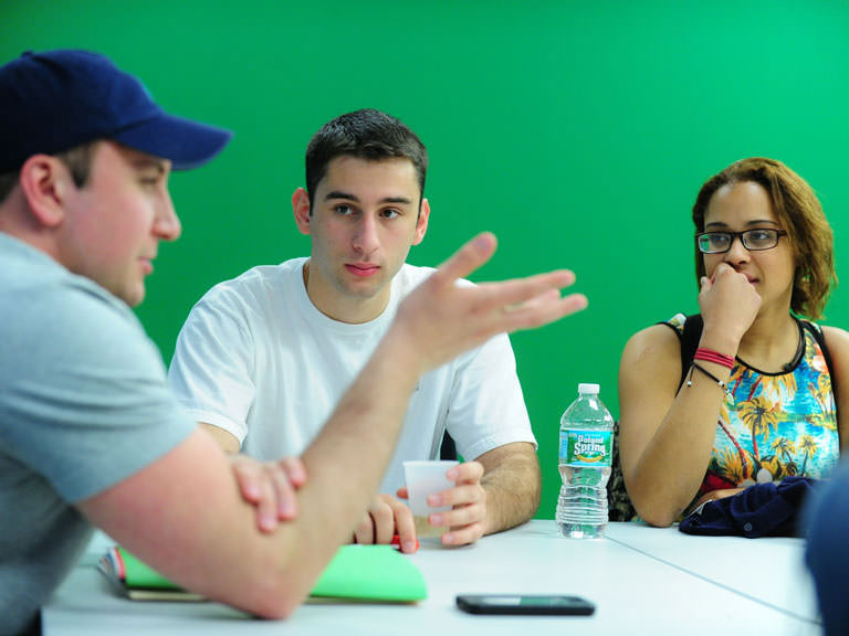 Professor engages students in discussion in a small classroom setting.