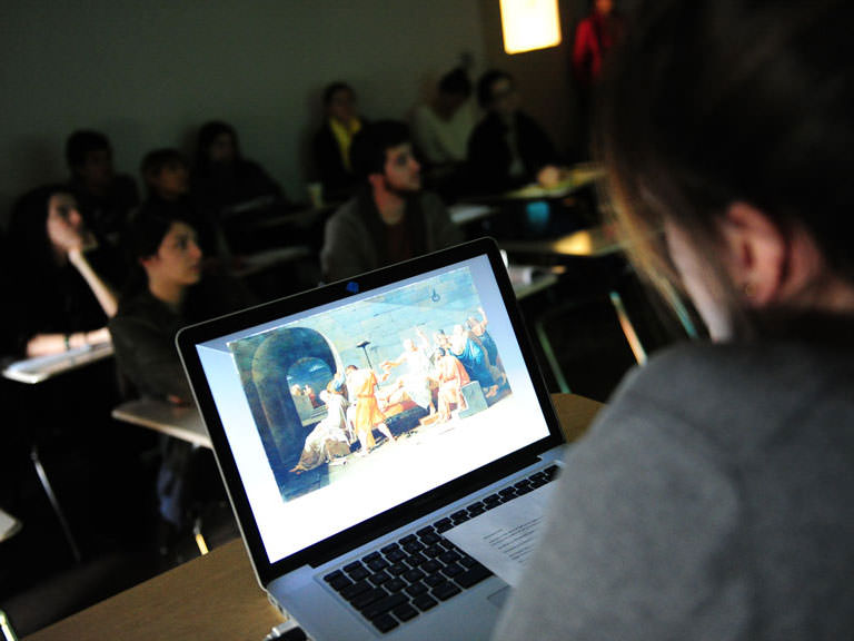 Students view a classical painting on the projector.