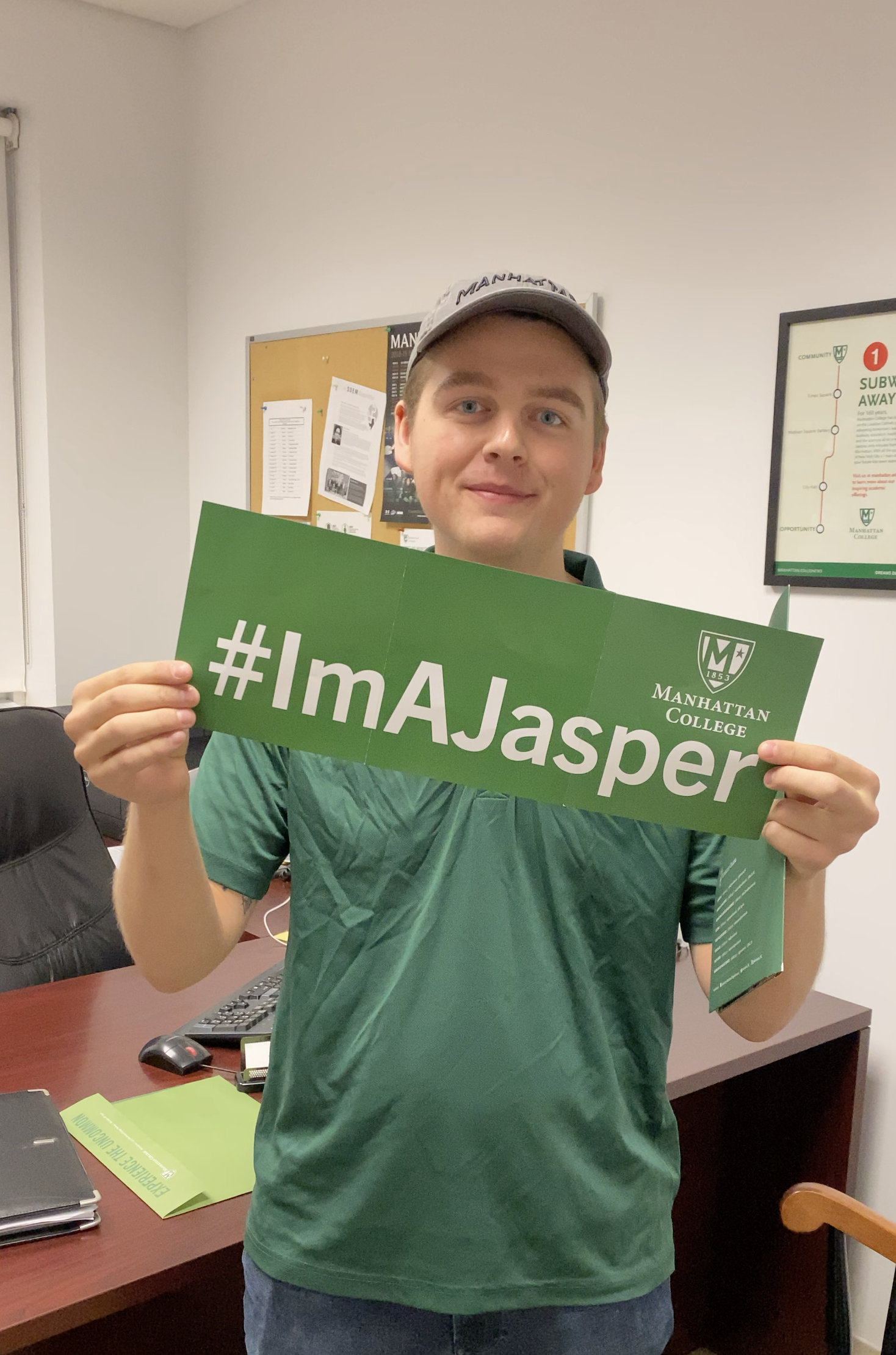 "Photograph of student holding green sign that states: ""#IamAJasper"""