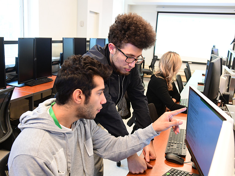 an image of two male students looking at computer screen together