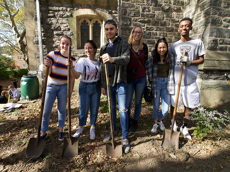 Students stand in park posing with shovels.