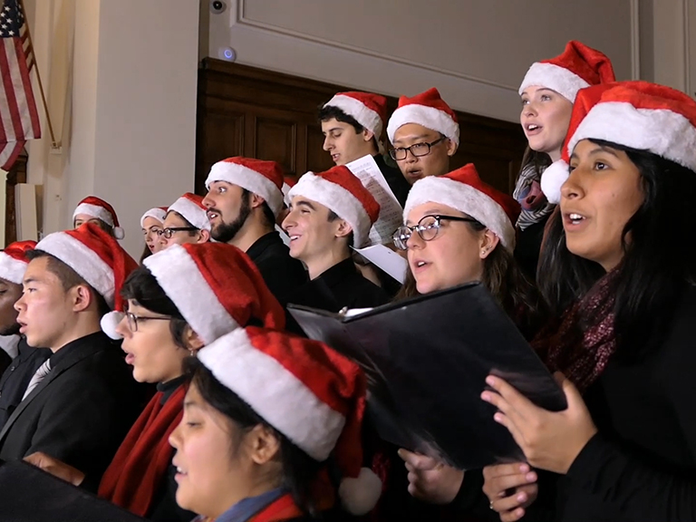 Group of students singing in santa hats