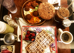 Image of waffle and other food items on lunch table of Riverdale restaurant.