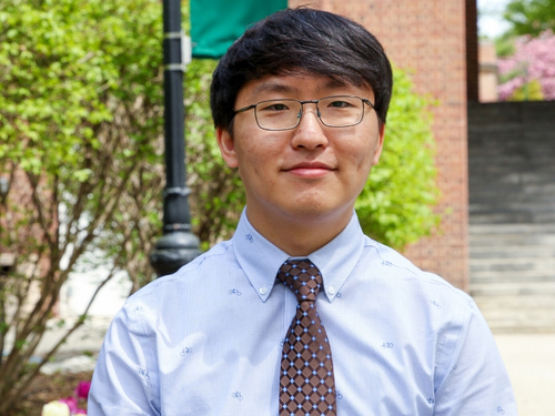 Hongbin Xu smiling in front of Manhattan College entrance.