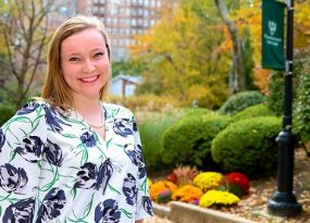 kerry cavanagh wearing flowered shirt standing in front of manhattan college campus