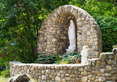 Manhattan College stone grotto with statue of Mary Mother of Godon campus.
