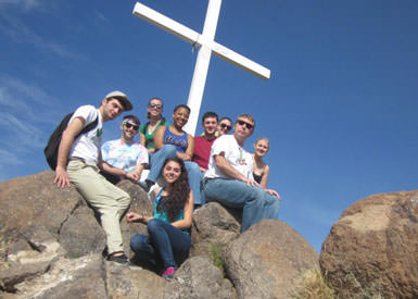 image of students in front of large cross