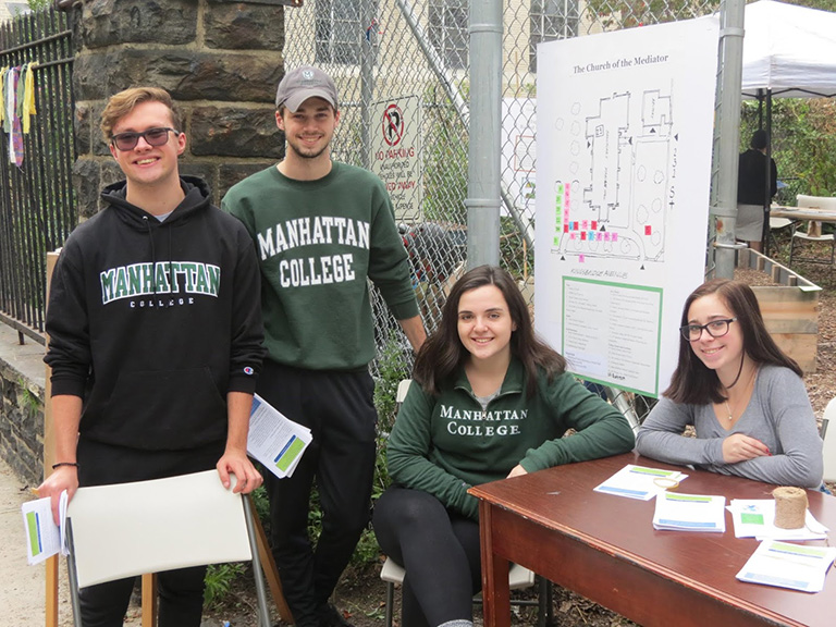 three students stand together wearing manhattan college sweatshirts