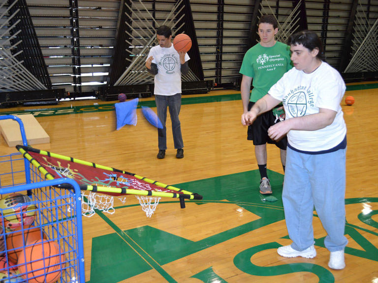 College students play basketball with special needs children.