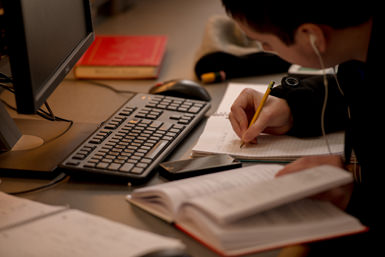 A student sitting at a computer desk with keyboard visible while writing in notebook.