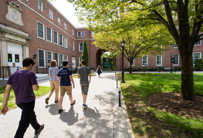 a group of four students walking on the quad