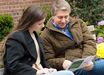 man in brown jacket sits with young woman with brown hair on bench