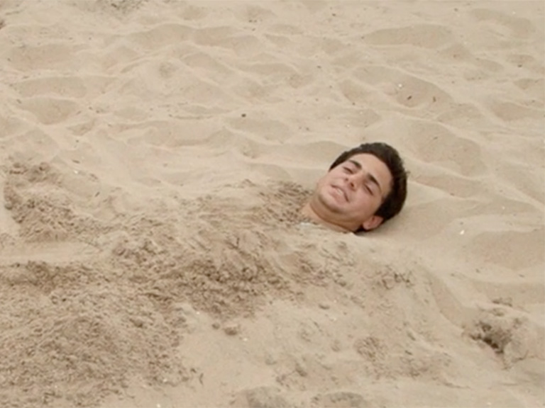 Matt Marcello buried in sand