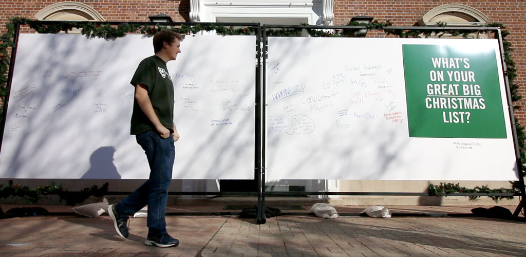 Participants walking by a white board on the quadrangle.