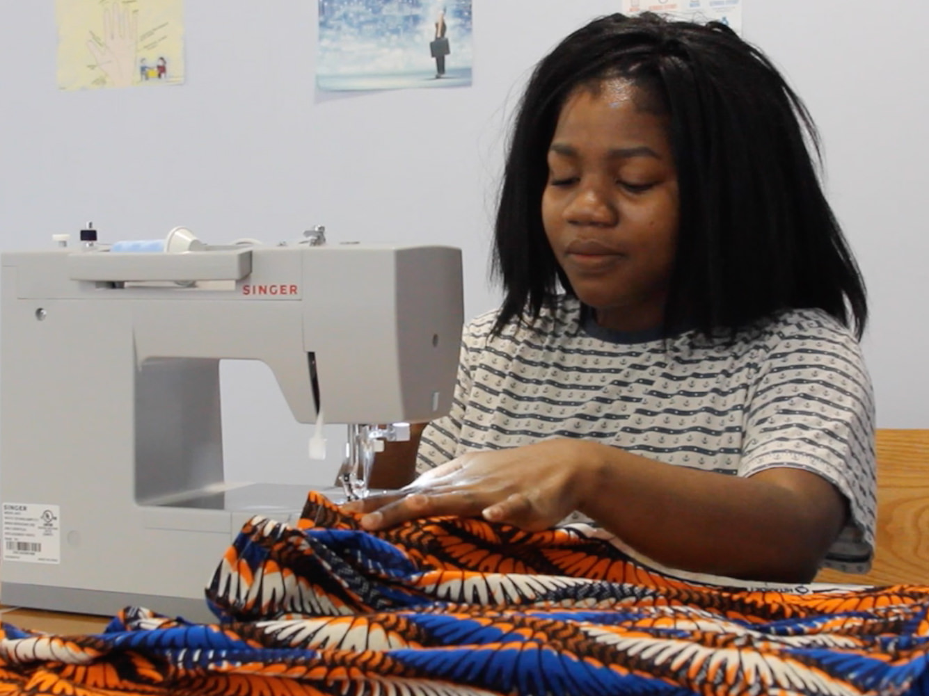 student designs clothes with sewing machine