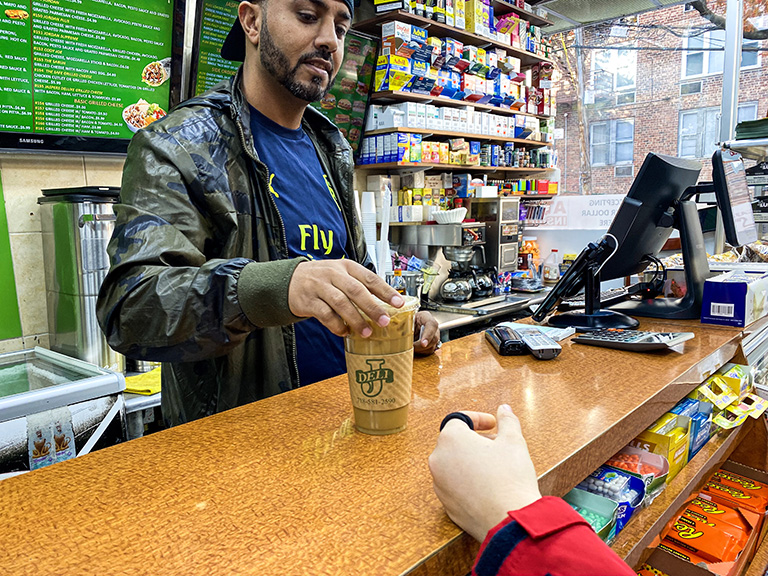 man handing an iced coffee across a deli counter to customer