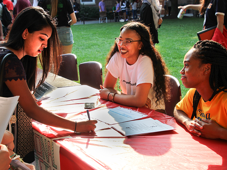 Students engage with each other at club and activities fair on campus.