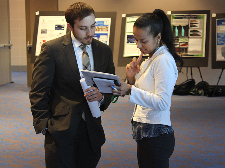 Two students discussing notes during a research poster presentation