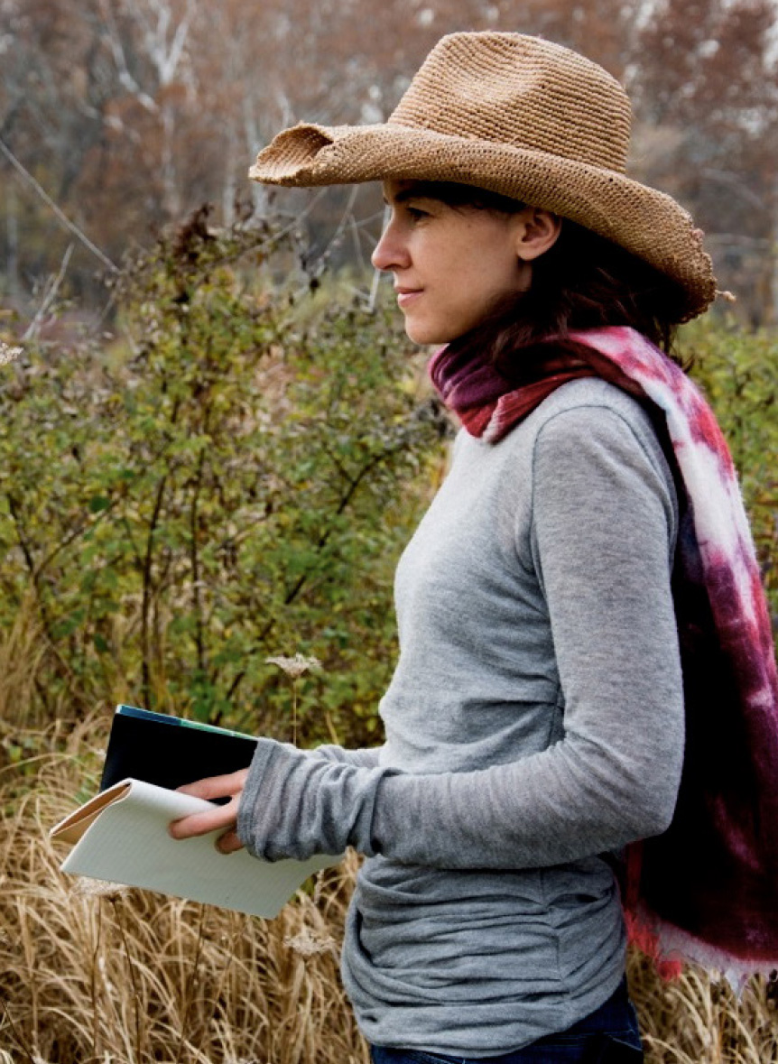 Hara Woltz standing in field with notebook