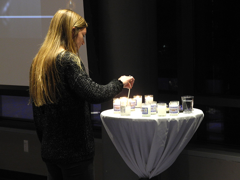 Student lighting candle at HGI Center event