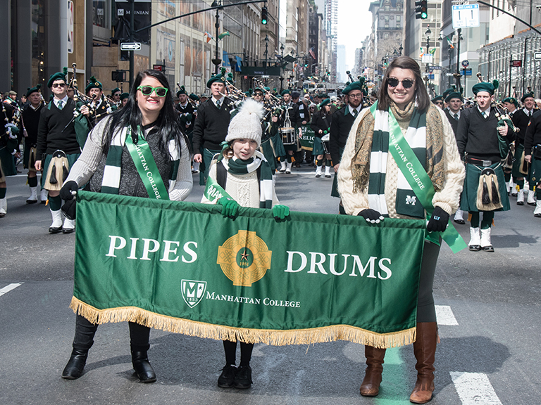 Students holding Pipes and Drums banner.