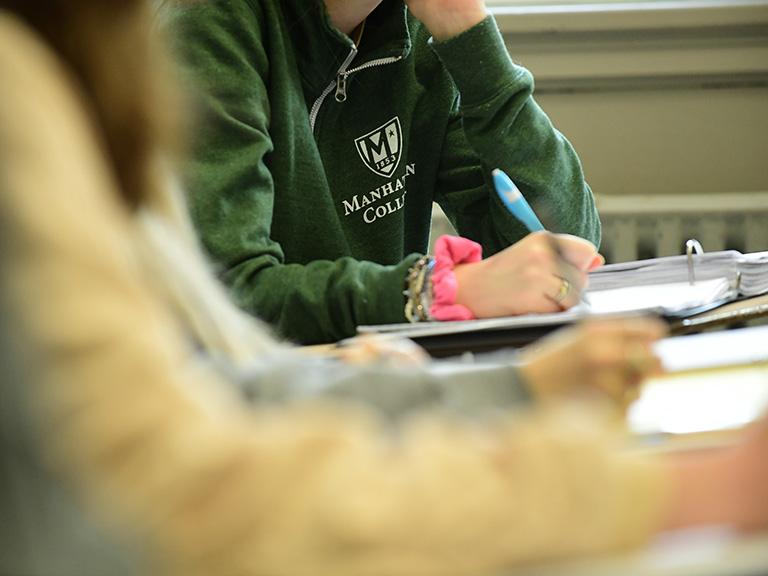 Manhattan College student in class wearing green College sweatshirt