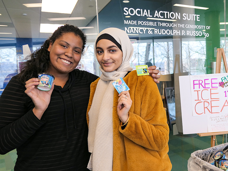 Two students in front of social action suite holding up ice cream for the ice cream social
