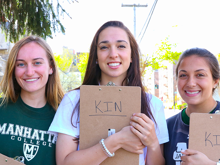 three women stand together holding brown clipboards