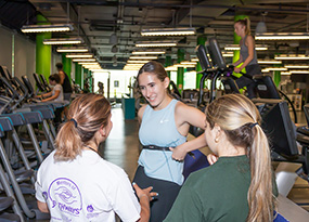 woman adjusting strap in gym
